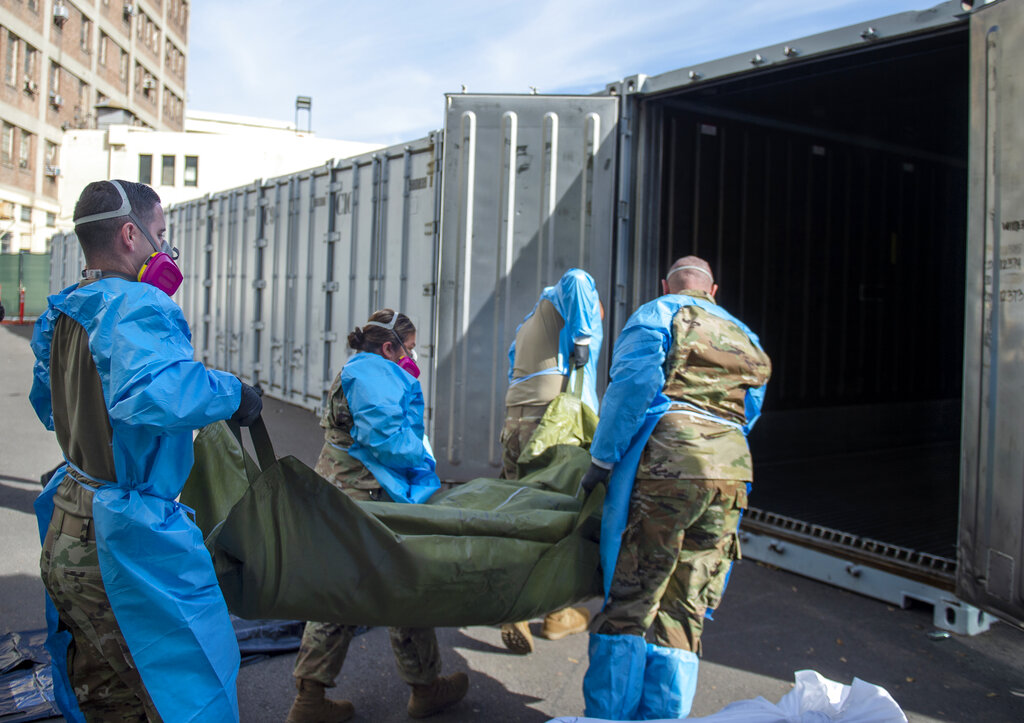 In this photo provided by the Los Angeles County Department of Medical Examiner-Coroner, National Guard members assist with processing COVID-19 deaths, placing the bodies into temporary storage at the medical examiner-coroner's office in Los Angeles. The seven-day rolling average of daily deaths is rising in 30 states and the District of Columbia, and on Monday, the U.S. was approaching 398,000, according to data collected by Johns Hopkins University, by far the highest of any country in the world. (Los Angeles County Department of Medical Examiner-Coroner via AP, File)