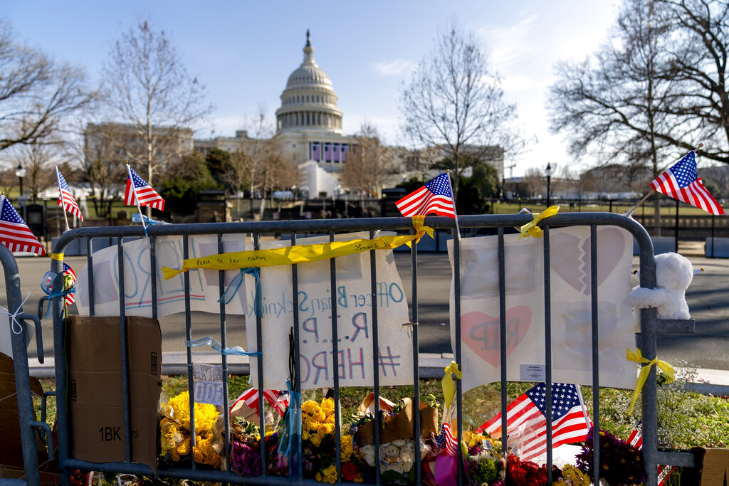 A memorial for Capitol Police Officer Brian D. Sicknick is visible near the Capitol Building on Capitol Hill in Washington, Thursday, Jan. 14, 2021. Officer Sicknick was killed by rioters in last Wednesday's attack on the Capitol Building. (AP Photo/Andrew Harnik)