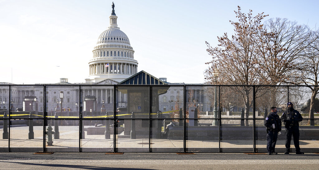 Capitol police officers stand outside of fencing that was installed around the exterior of the Capitol grounds, Thursday, Jan. 7, 2021 in Washington. (AP Photo/John Minchillo)