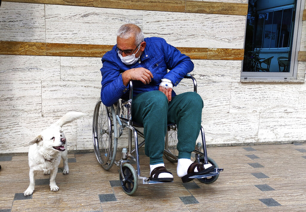 Cemal Senturk, owner of Boncuk, outside of a medical care facility in the Black Sea city of Trabzon, Turkey, Wednesday, Jan. 20, 2021. Boncuk has spent five days waiting in front of the hospital where her sick owner was receiving treatment. Senturk was discharged from the hospital later on Wednesday and returned home with Boncuk.(DHA via AP)