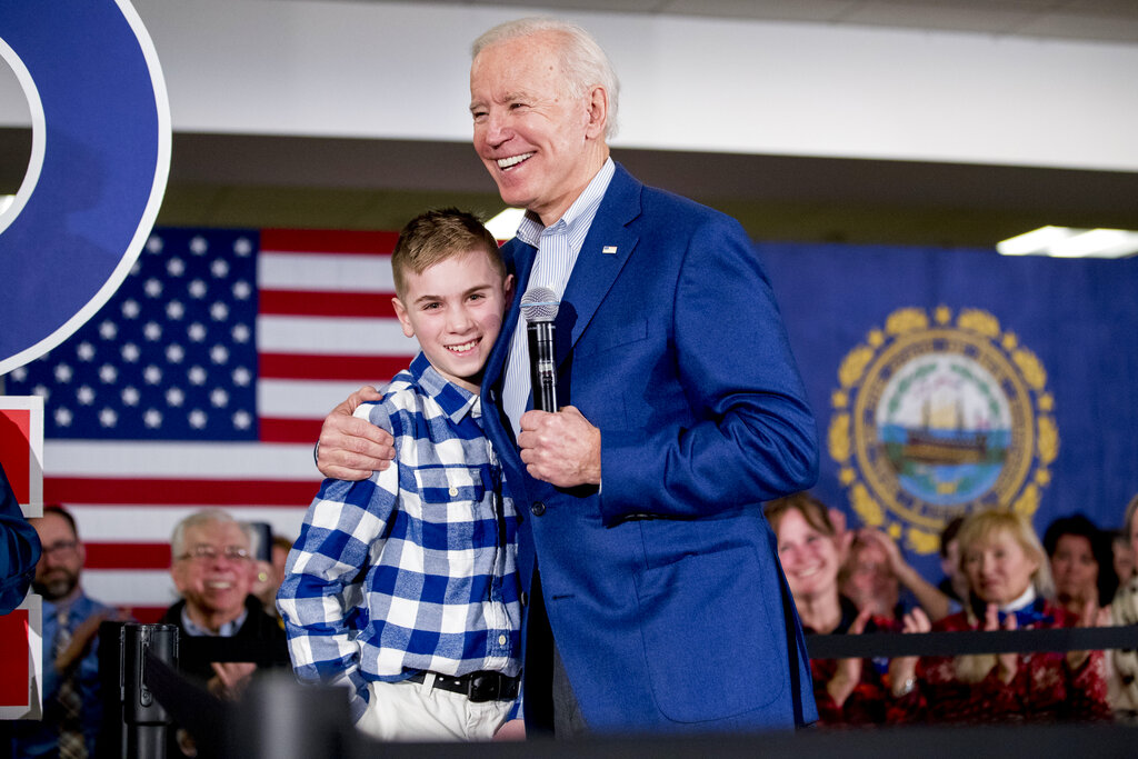 "Joe Biden hugs Brayden Harrington at a campaign stop in Gilford, N.H. on Feb. 10, 2020. Harrington, who will be part of a primetime inaugural special, has a book coming out this summer. His picture story ""Brayden Speaks Up"" will be released Aug. 10. (AP Photo/Andrew Harnik, File)"
