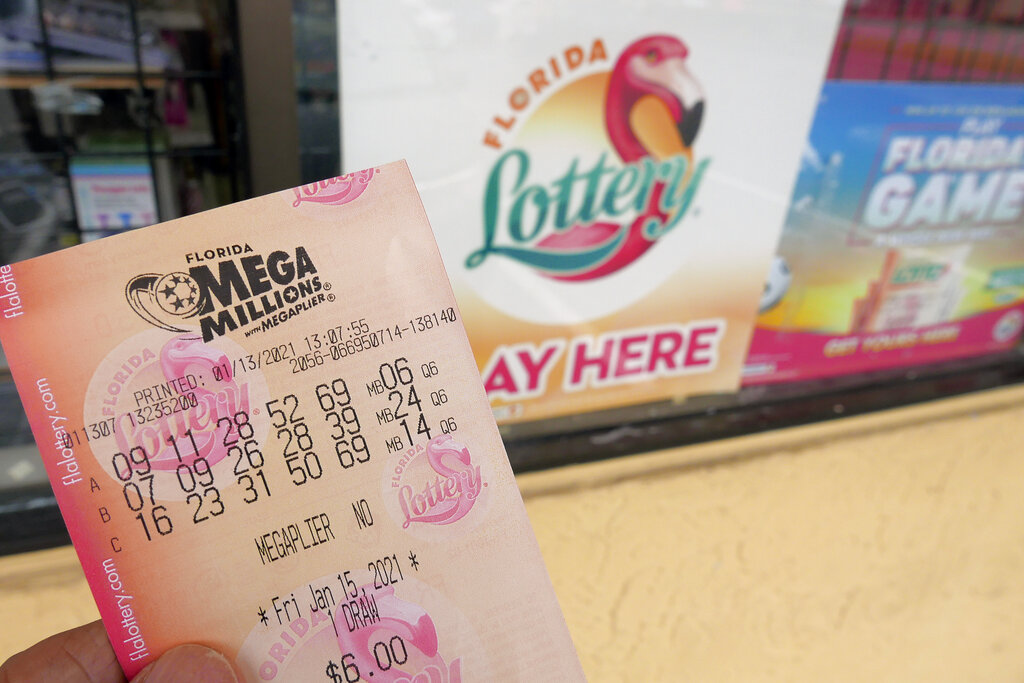 A customer shows off a Mega Millions lottery ticket after purchasing it, Wednesday, Jan. 13, 2021, in Orlando, Fla. (AP Photo/John Raoux)