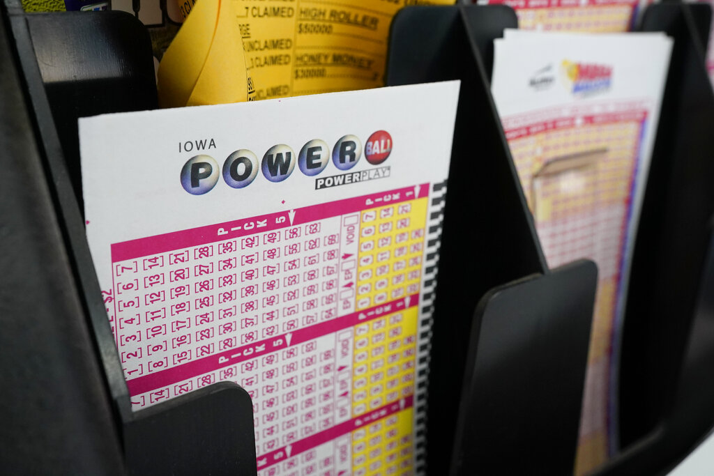 Blank forms for the Powerball lottery sit in a bin at a local grocery store, Tuesday, Jan. 12, 2021, in Des Moines, Iowa. (AP Photo/Charlie Neibergall)