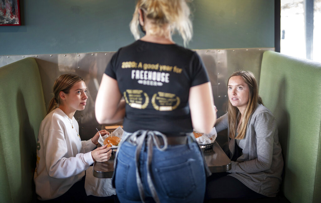 Grace Mathre, server at Longfellow Grill, checks on University of St. Thomas students Lundsey Schulz and Maren Daggett in Minneapolis on Jan. 11. As the U.S. finds itself in the most lethal phase of the coronavirus outbreak yet, governors and local officials in hard-hit parts of the country are showing little willingness to impose any new restrictions on businesses to stop the spread. (Glen Stubbe/Star Tribune via AP, File)