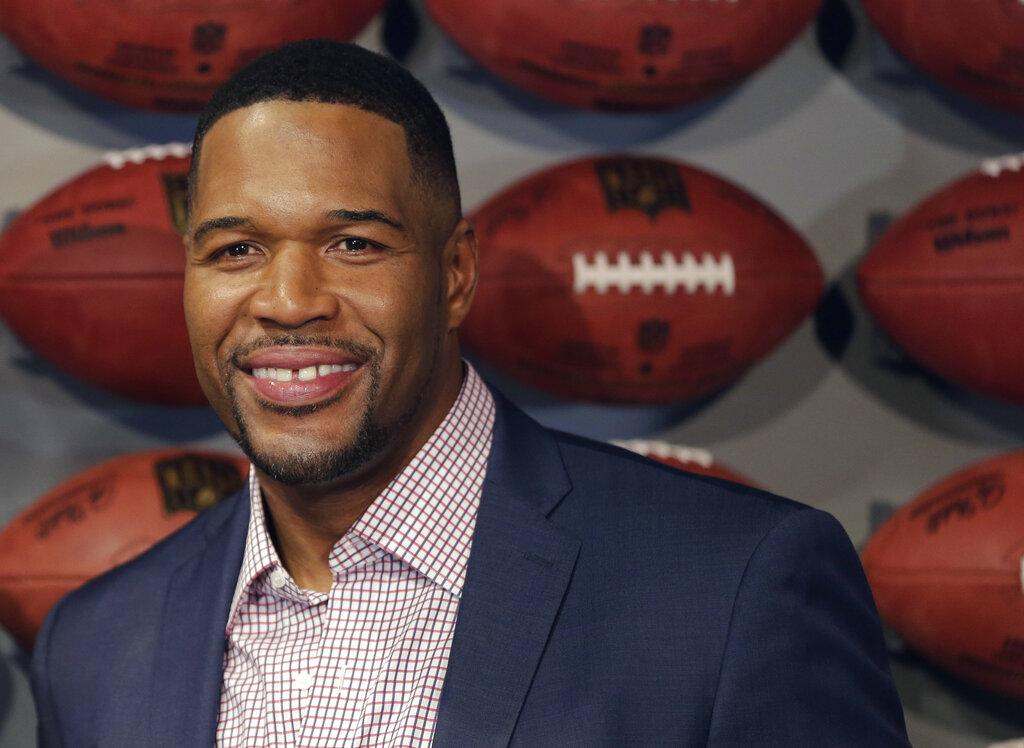 "Former New York Giant Michael Strahan poses for a picture at the opening of ""NFL Experience"" in Times Square, New York. Pro Football Hall of Famer and ""Good Morning America"" host Michael Strahan has tested positive for COVID-19 and is self-quarantining, according to people familiar with the situation. They spoke to The Associated Press on condition of anonymity Wednesday, Jan. 27, 2021 because of medical restriction issues. (AP Photo/Seth Wenig, File)"