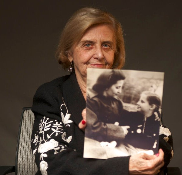 Tova Friedman, an 82-year-old Polish-born Holocaust survivor holds a photograph of herself as a child with her mother, who also survived the Nazi death camp Auschwitz, in 2019. Friedman is delivering a warning against rising hatred in the world during an online commemoration on Wednesday, the 76th anniversary of the liberation of Auschwitz by Soviet troops at end of World War II. The commemorations for the victims of the Holocaust at the International Holocaust Remembrance Day, marking the liberation of Auschwitz-Birkenau on Jan. 27, 1945, will be mostly online in 2021 due to the coronavirus pandemic. (World Jewish Congress via AP)