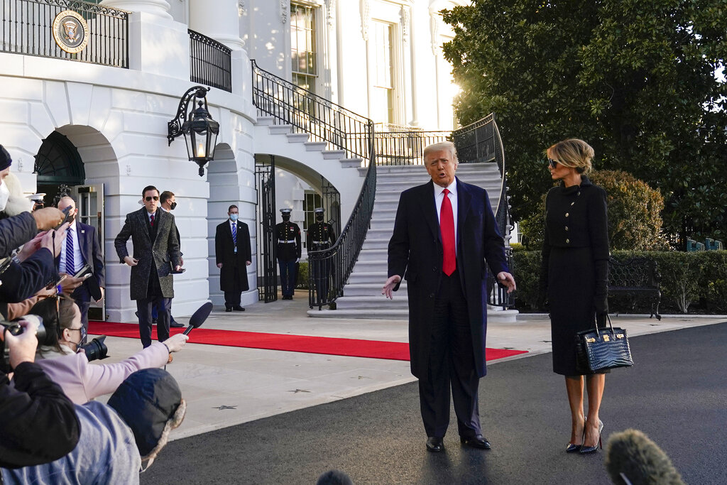President Donald Trump and first lady Melania Trump stop to talk with the media as they walk to board Marine One on the South Lawn of the White House Wednesday morning. (AP Photo/Alex Brandon)