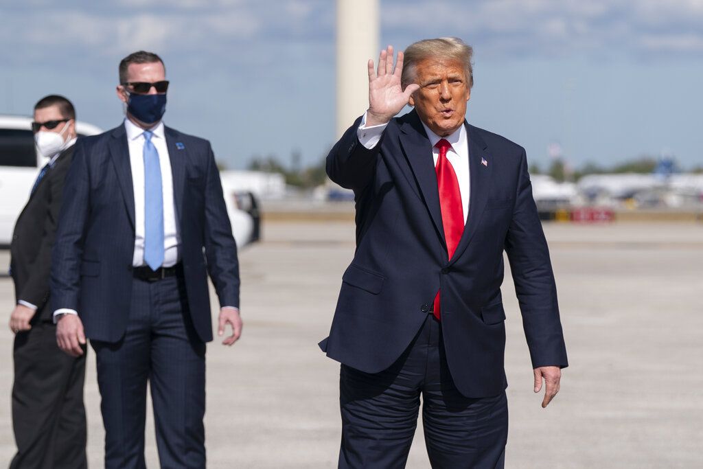 Former President Donald Trump waves to the members of the media on arrival at Palm Beach International Airport in West Palm Beach, Fla., Wednesday, Jan. 20, 2021. (AP Photo/Manuel Balce Ceneta)