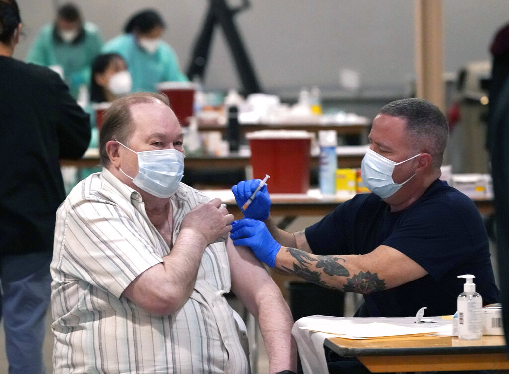 Howard Holland, 82, receives his first dose of the COVID-19 vaccine from Wes Vaughn at the Dallas County mass vaccination site at Fair Park Wednesday, Jan. 20, 2021, in Dallas. (AP Photo/LM Otero)