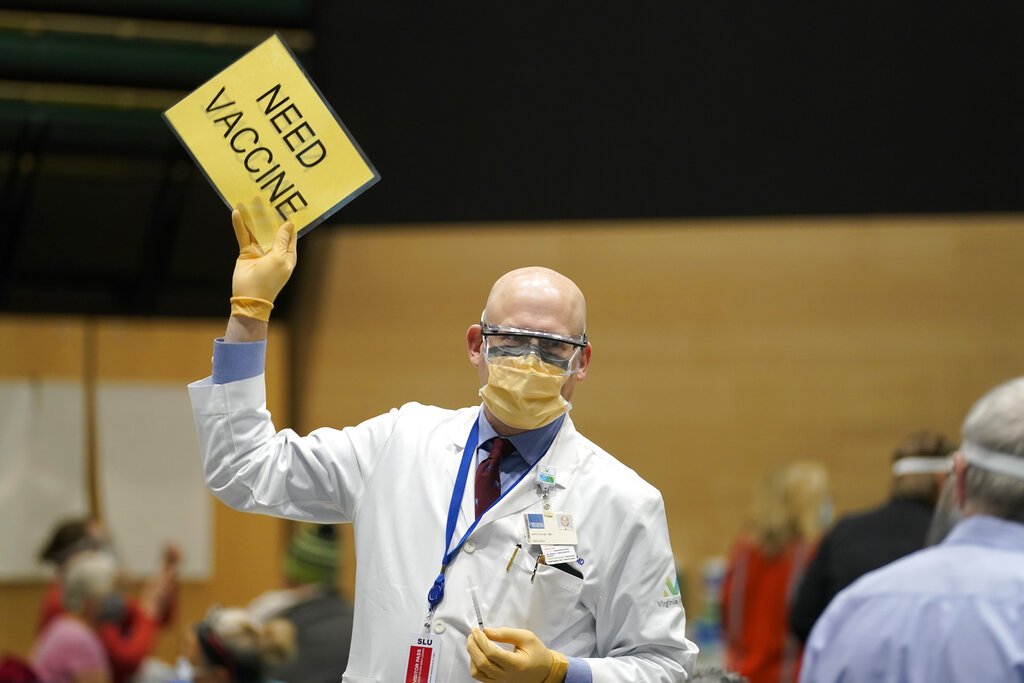"Dr. John Corman, the chief clinical officer for Virginia Mason Franciscan Health, holds a sign that reads ""Need Vaccine"" to signal workers to bring him more doses of the Pfizer vaccine for COVID-19 as he works at a one-day vaccination clinic set up in an Amazon.com facility in Seattle. An increasing number of COVID-19 vaccination sites around the U.S. are canceling appointments because of vaccine shortages in a rollout so rife with confusion and unexplained bottlenecks. (AP Photo/Ted S. Warren, File)"