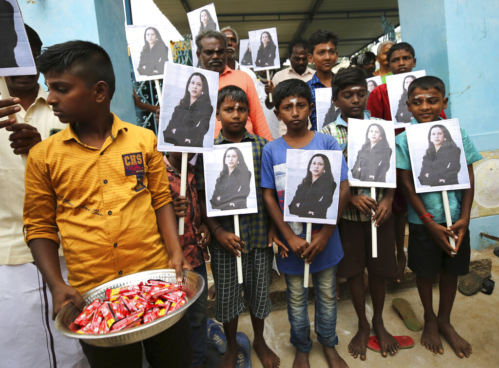 A child holds a tray of chocolates as others hold portraits of U.S. Vice President-elect Kamala Harris after participating in special prayers ahead of her inauguration, at a Hindu temple in Thulasendrapuram, the hometown of Harris' maternal grandfather, south of Chennai, Tamil Nadu state, India, Wednesday, Jan. 20, 2021. A tiny, lush-green Indian village surrounded by rice paddy fields was beaming with joy Wednesday hours before its descendant, Kamala Harris, takes her oath of office and becomes the U.S. vice president. (AP Photo/Aijaz Rahi)