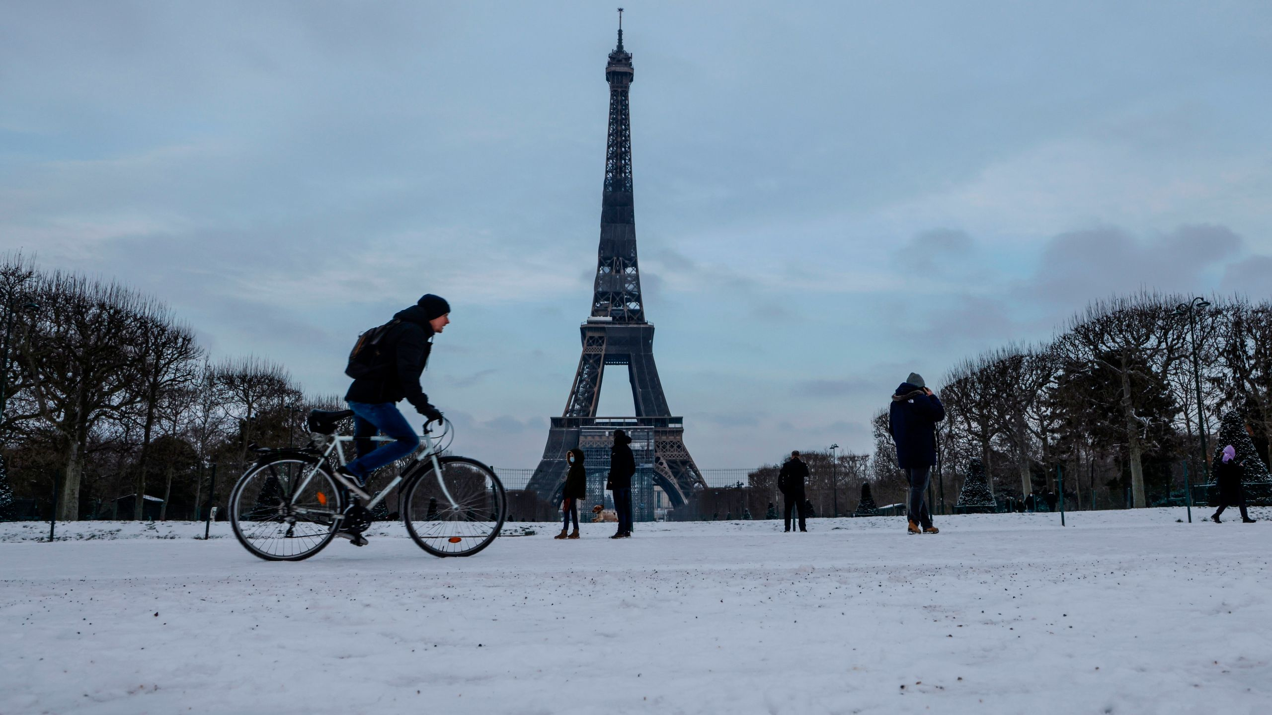 A cyclist rides past the Eiffel Tower following a light overnight snowfall in Paris on February 10, 2021. (Photo by LUDOVIC MARIN/AFP via Getty Images)