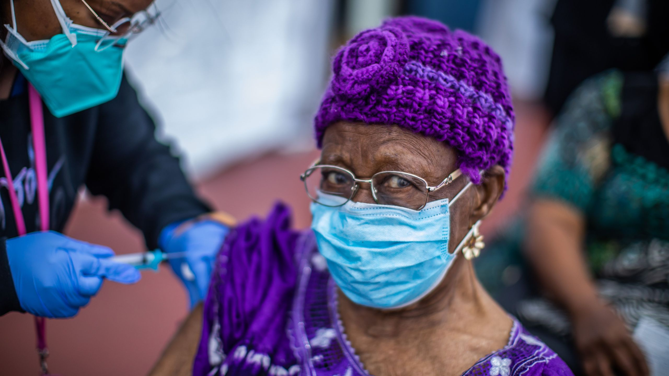 Registered Nurse Ebony Thomas administers a Moderna Covid-19 vaccine to Cecilia Onwytalu, 89, at Kedren Community Health Center, in South Central Los Angeles on February 16, 2021. (Photo by APU GOMES/AFP via Getty Images)