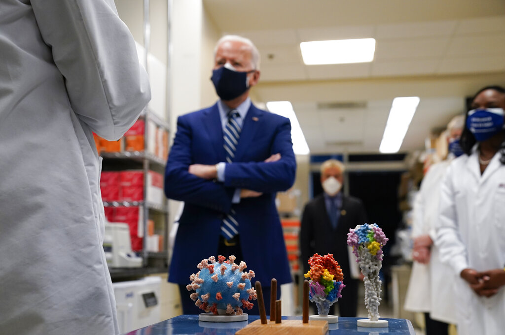 President Joe Biden visits the Viral Pathogenesis Laboratory at the National Institutes of Health (NIH) in Bethesda, Md., on Thursday, Feb. 11. At bottom center is a model of the COVID-19 virus. (AP Photo/Evan Vucci)