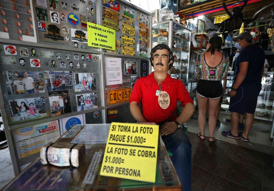 Tourists buy souvenirs of the late drug baron Pablo Escobar, featured as a statue with a sign that says one will be charged for taking photos inside a store in Doradal, Colombia. Escobar and his Medellin Cartel are long dead, but one of the zoo's prized specimens is flourishing in the tropical countryside and wetlands in and around the palace-turned-theme park. (AP Photo/Fernando Vergara)