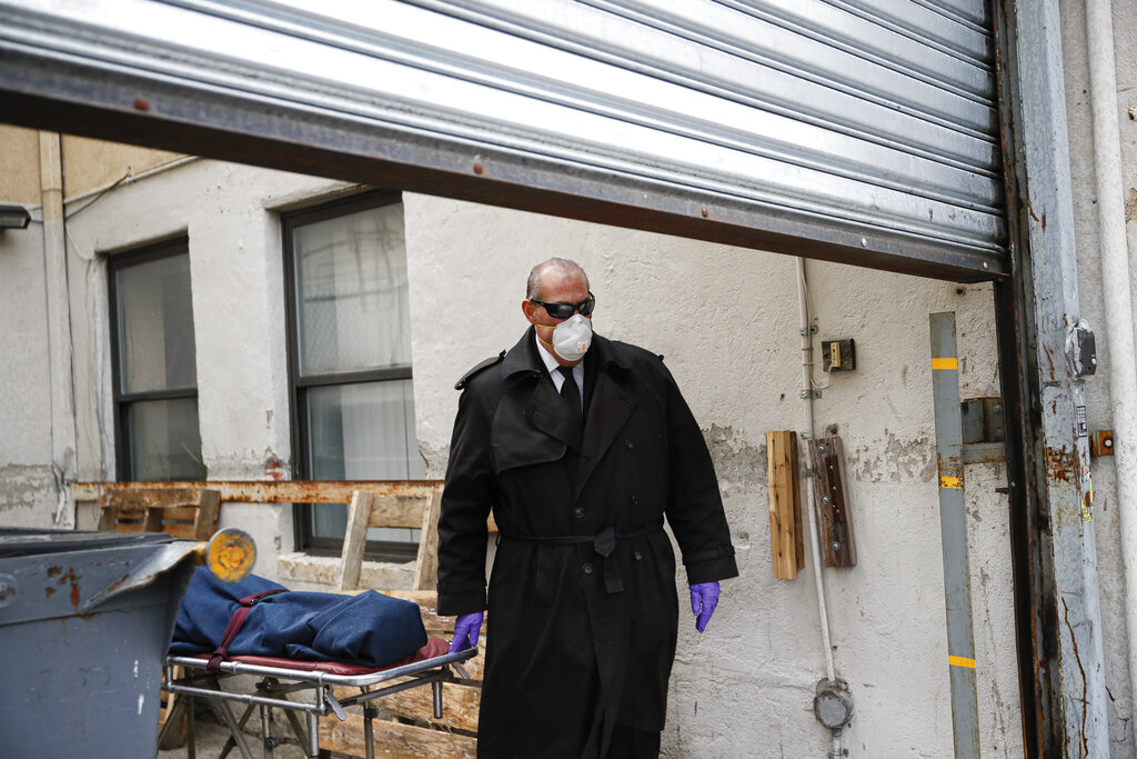 Funeral director Tom Cheeseman collects a body from a nursing home in the Brooklyn borough of New York in April 2020. As the coronavirus takes a devastating toll on seniors in nursing homes, many attorneys are turning down grieving families seeking to sue long-term care providers for wrongful death. (AP Photo/John Minchillo, File)