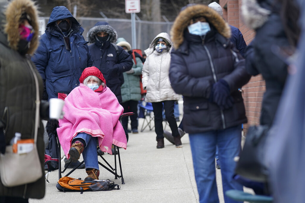 Judy McKim, center left, waits in line with others for the COVID-19 vaccine in Paterson, N.J. The first people arrived around 2:30 a.m. for the chance to be vaccinated at one of the few sites that does not require an appointment. (AP Photo/Seth Wenig)