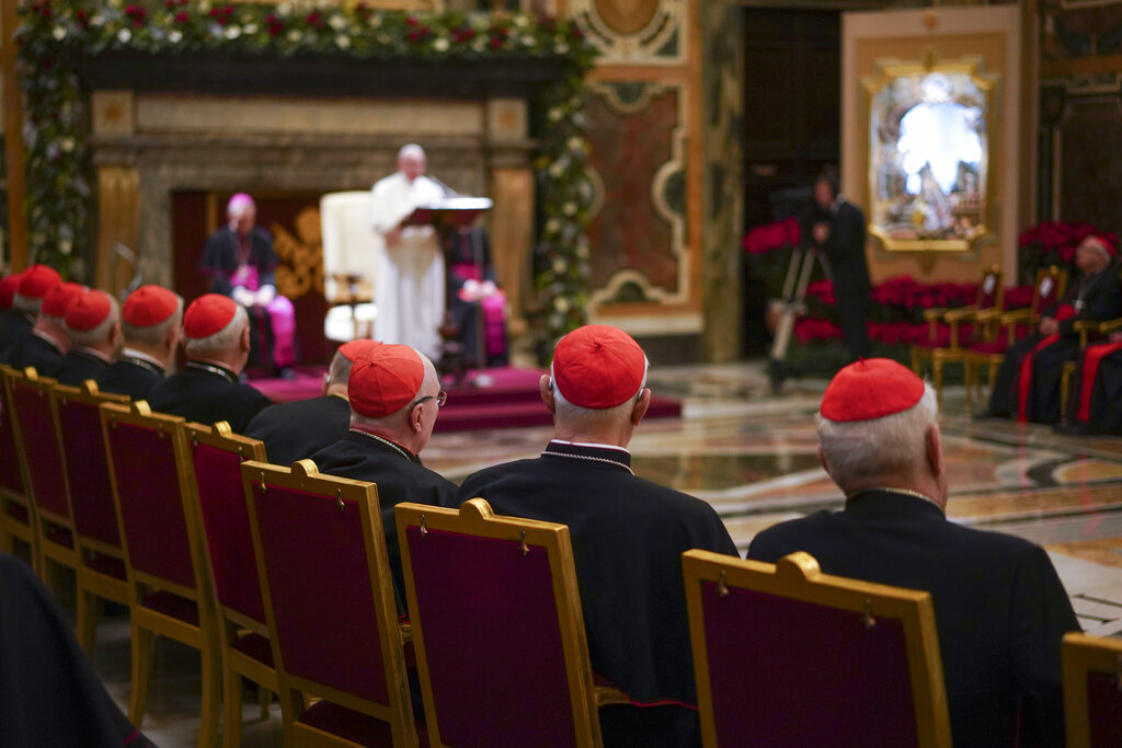 """Cardinals listen as Pope Francis, background, delivers his Christmas greetings to the Roman Curia, in the Clementine Hall at the Vatican, Saturday, Dec. 21, 2019. Pope Francis has ordered pay cuts for Holy See employees, including slashing cardinals' salaries by 10%. Francis in a letter made public by the Vatican on Wednesday, March 24, 2021, noted that the pandemic emergency """"negatively impacted all sources of revenue"""" for the Holy See and Vatican City State. (AP Photo/Andrew Medichini, File)"""