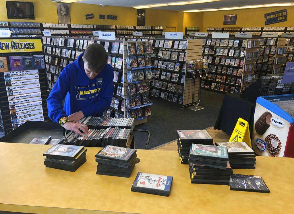 Employee Ryan Larrew alphabetizes returned movies before re-shelving them at the last Blockbuster store on the planet in Bend, Oregon in 2019. The new Netflix movie called The Last Blockbuster that began airing March 15 is generating interest in the store, which became the last Blockbuster location on Earth when a location in Perth, Australia shut its doors in 2019. (AP Photo/Gillian Flaccus, File)