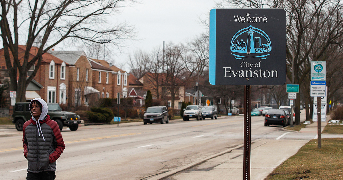 A man walks by a sign welcoming people to the city of in Evanston, Illinois, on March 16, 2021. The Chicago suburb is set to become the first place in the United States to provide reparations to its Black residents, with a plan to distribute $10 million over the next decade. (Photo by KAMIL KRZACZYNSKI/AFP via Getty Images)