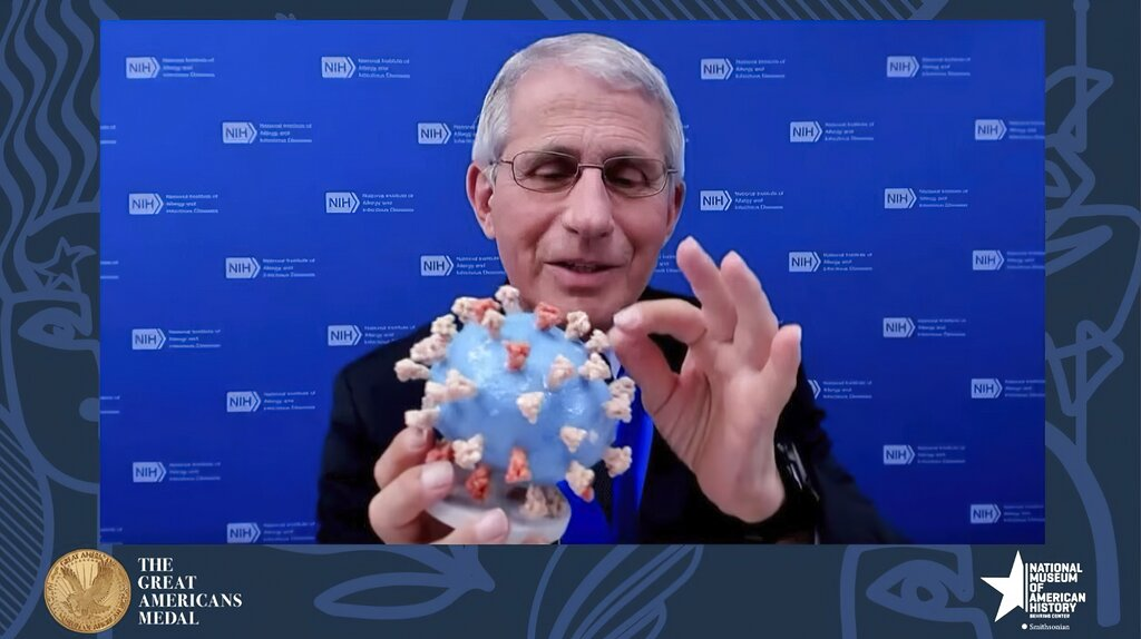 Dr. Anthony Fauci, director of the National Institute of Allergy and Infectious Diseases and chief medical adviser to the president, holds his personal 3D model of the COVID-19 virus that he is donating to the Smithsonian's National Museum of American History. Fauci presented the donation Tuesday night in a virtual ceremony honoring him with the museum's Great Americans Medal. (Smithsonian's National Museum of American History via AP)