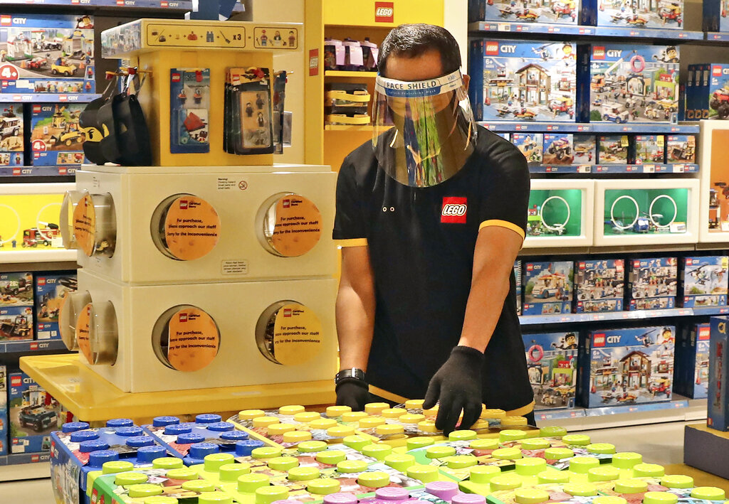 An employee wearing protective gear arrange boxes of Lego at a toy store in Jakarta, Indonesia. Sales of Lego sets surged in 2020 as more children stayed home during global pandemic lockdowns - and parents bought the colorful plastic brick toys to keep them entertained during weeks of isolation. The privately-held Danish company said its net profit rose 19% to 9.9 billion kroner ($1.6 billion) as sales jumped 21% and it grew its presence in its 12 largest markets. (AP Photo/Tatan Syuflana, file)