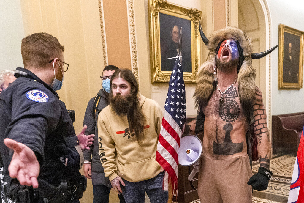 Supporters of former President Donald Trump, including Jacob Chansley, right with fur hat, are confronted by U.S. Capitol Police officers outside the Senate Chamber inside the Capitol in Washington. Chansley made a written apology from jail, asking for understanding as he was coming to grips with his actions. (AP Photo/Manuel Balce Ceneta, File)