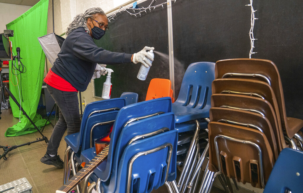Latisha Bledsoe cleans chairs in the music room at Manchester Academic Charter School on March 4, 2021. The school is planning to return students to the classroom in a hybrid schedule at the end of March. (Andrew Rush/Pittsburgh Post-Gazette via AP, File)