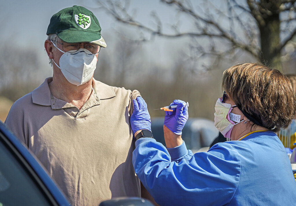 Joe Crowley of O'Hara Township, Pa., wears a St. Patrick's Day cap while receiving a vaccination from registered nurse Kathleen Marouse at a drive-up COVID-19 vaccination clinic at the UPMC Lemieux Sports Complex in Cranberry Township, Pa., a Pittsburgh suburb. (Steve Mellon/Pittsburgh Post-Gazette via AP)