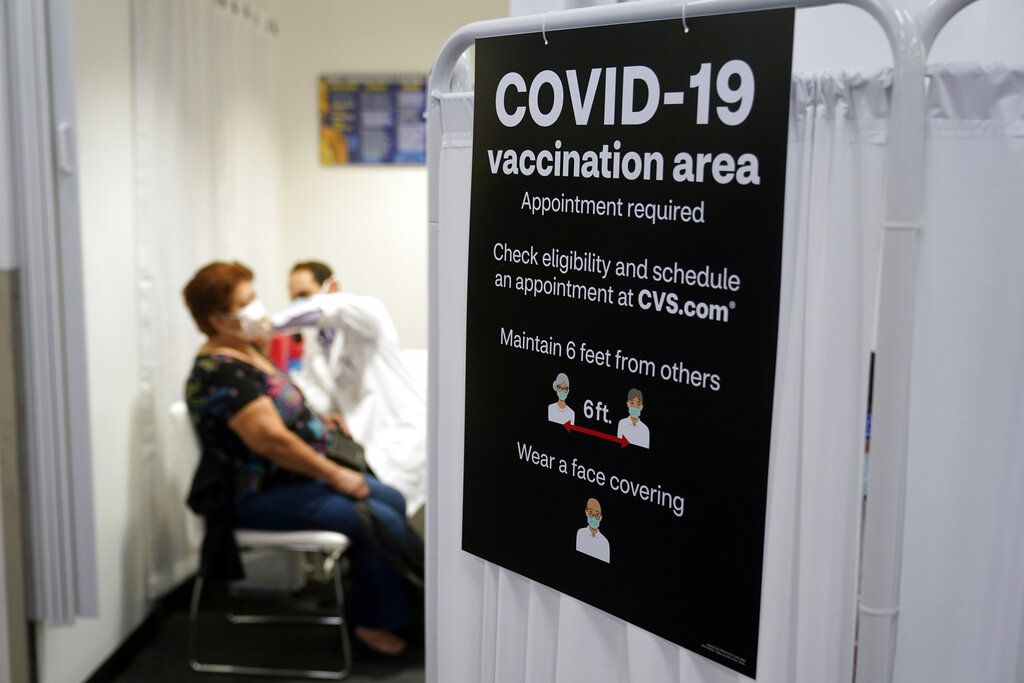 A patient receives a shot of the Moderna COVID-19 vaccine next to a guidelines sign at a CVS Pharmacy branch in Los Angeles. More than 27 million Americans fully vaccinated against the coronavirus will have to keep waiting for guidance from U.S. health officials for what they should and shouldn't do. The Biden administration said Friday it's focused on getting the guidance right and accommodating emerging science. (AP Photo/Marcio Jose Sanchez, File)