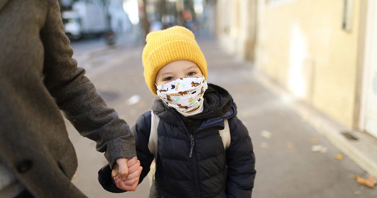 A little girl wearing a protective face mask, holding the hand of her mother in the street before to go to school