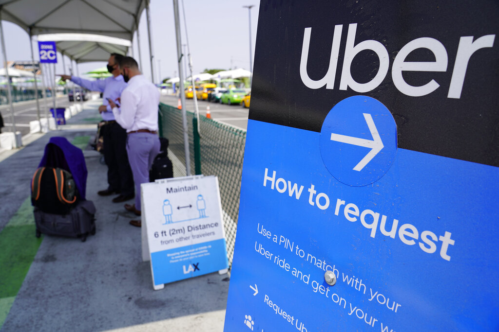 Travelers request an Uber ride at Los Angeles International Airport's LAX-it pick up terminal. (AP Photo/Damian Dovarganes, File)