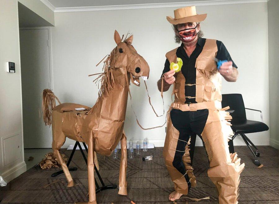 David Marriott posa con su caballo de papel en su habitación de hotel en Brisbane, Australia. Mientras estaba en cuarentena dentro de su habitación de hotel en Brisbane, comenzó a hacer un traje de vaquero con las bolsas de papel en las que se entregaban sus comidas. Su proyecto se expandió para incluir un caballo y un villano de película adhesiva con el que tiene aventuras diarias, en imágenes que han ganado un gran impacto. seguimiento en línea. (David Marriott vía AP)