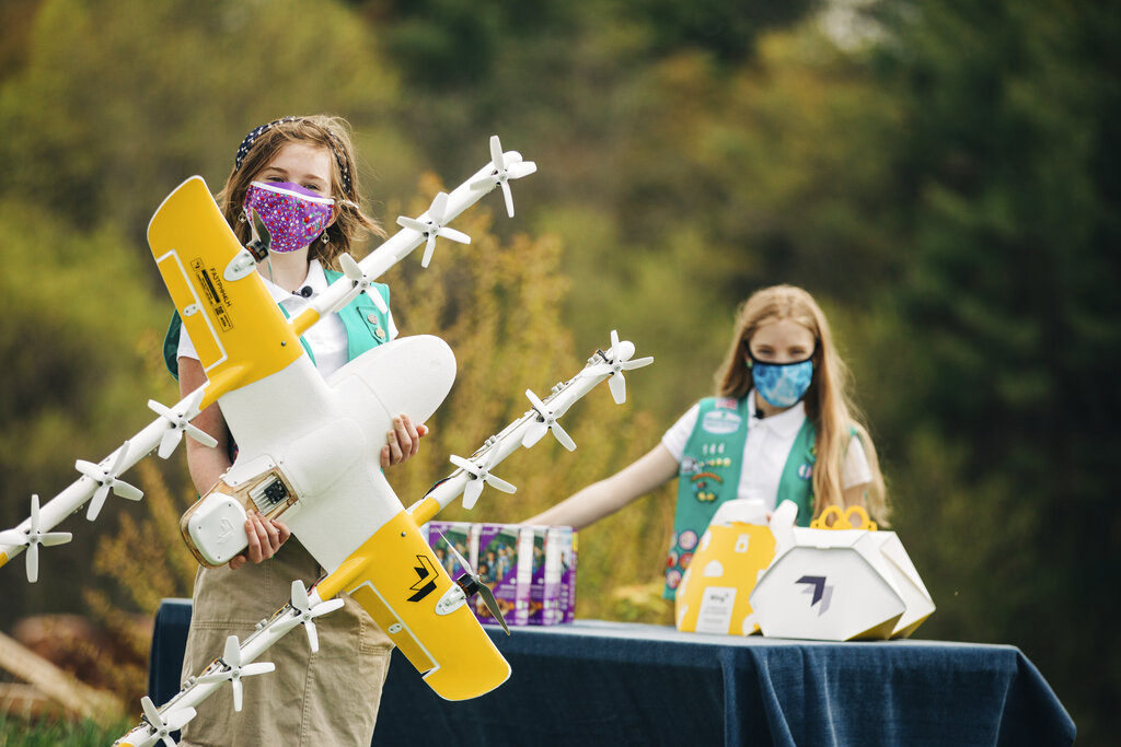 In this image provided by Wing LLC., Girl Scouts Alice Goerlich, right, and Gracie Walker pose with a Wing delivery drone in Christiansburg, Va. The company is testing drone delivery of Girl Scout cookies in the area. (Sam Dean/ Wing LLC via AP)