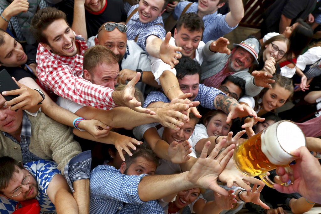 People reach out for a glass of beer during the opening of the 186th 'Oktoberfest' beer festival in Munich, Germany in 2019. Bavarian officials have announced Monday they have canceled Oktoberfest festivities for the second year in a row due to concerns over the spread of the coronavirus global pandemic. (AP Photo/Matthias Schrader, FILE)