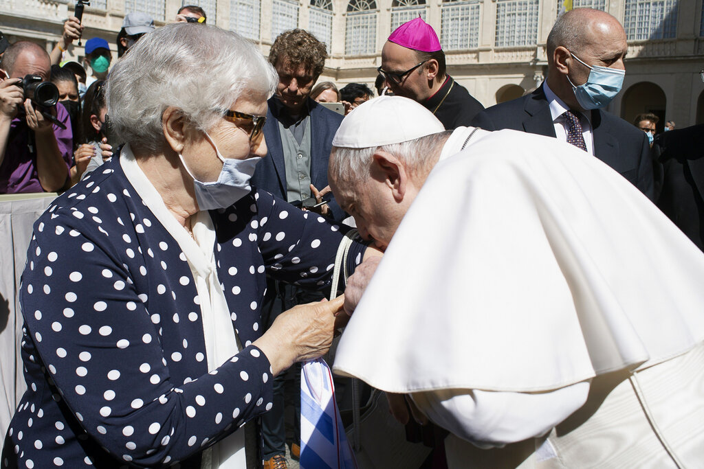 """Pope Francis kisses a tattoo on the arm of Holocaust survivor Lidia Maksymowicz, a Polish citizen who was deported to Auschwitz from her native Belarus, during his weekly general audience at the Vatican. Maksymowicz told Vatican News that she did not exchange words with the pope. She said """"we understood each other with a glance.""""  (Vatican Media via AP)"""