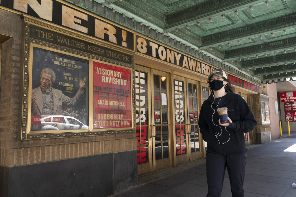 A woman walks past the Walter Kerr Theatre, Thursday, May 6, 2021, in New York where Hadestown was showing before the coronavirus pandemic forced its closing a year ago. (AP Photo/Mark Lennihan)