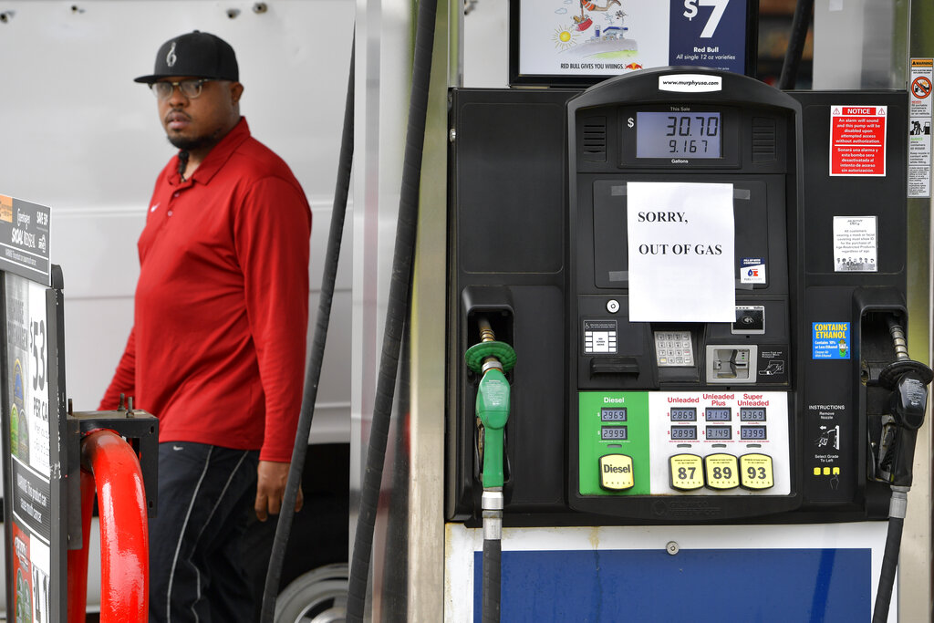 A man leaves a Murrphy Oil gas station as pumps are seen out of gas on Tuesday in Kennesaw, Ga. Colonial Pipeline, which delivers about 45% of the fuel consumed on the East Coast, halted operations last week after revealing a cyberattack that it said had affected some of its systems.(AP Photo/Mike Stewart)