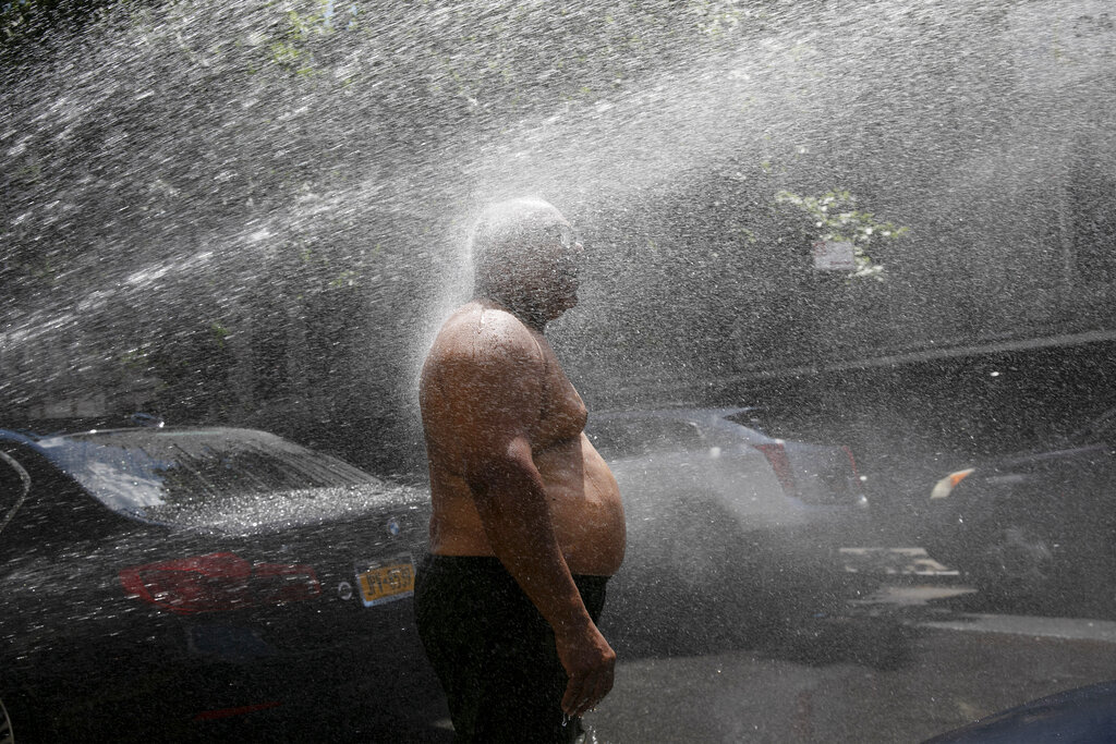 Rey Gomez cools off in the spray from a fire hydrant in New York on July 28, 2020, as the city opened more than 300 fire hydrants with sprinkler caps to help residents cool off during a heat wave. According to a study published Tuesday, May 25, 2021 inNature Communications, during the summer of 2017 in nearly all large urban areas, people of color are exposed to more extreme urban heat than white people. (AP Photo/Mark Lennihan, File)