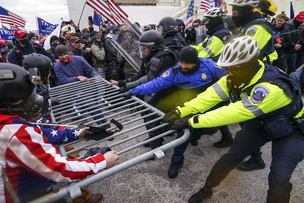 Supporters of then-President Donald Trump try to break through a police barrier, at the Capitol in Washington. (AP Photo/John Minchillo, File)
