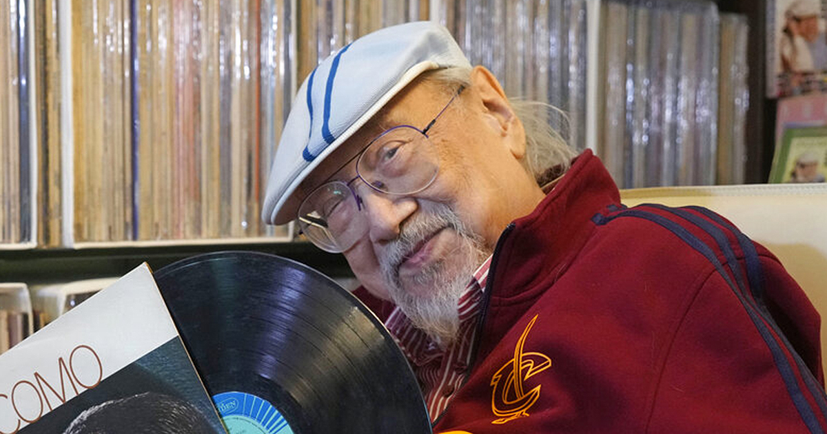 """Ray Cordeiro, 96, shows a vinyl record at his home in Hong Kong. Cordeiro has been named the world's """"most durable DJ"""" by the Guinness Book of World Records. (AP Photo/Kin Cheung)"""