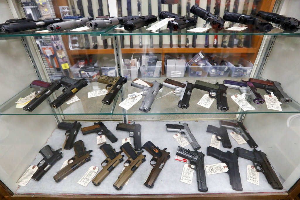 Semi-automatic handguns are displayed at shop in New Castle, Pa. The number of people stopped from buying guns though the U.S. background check system hit an all-time high of more than 300,000 last year amid a surge of firearm sales, according to new records obtained by the group Everytown for Gun Safety. The FBI numbers provided to The Associated Press show the background checks blocked nearly twice as many gun sales in 2020 as in the year before. (AP Photo/Keith Srakocic, File)