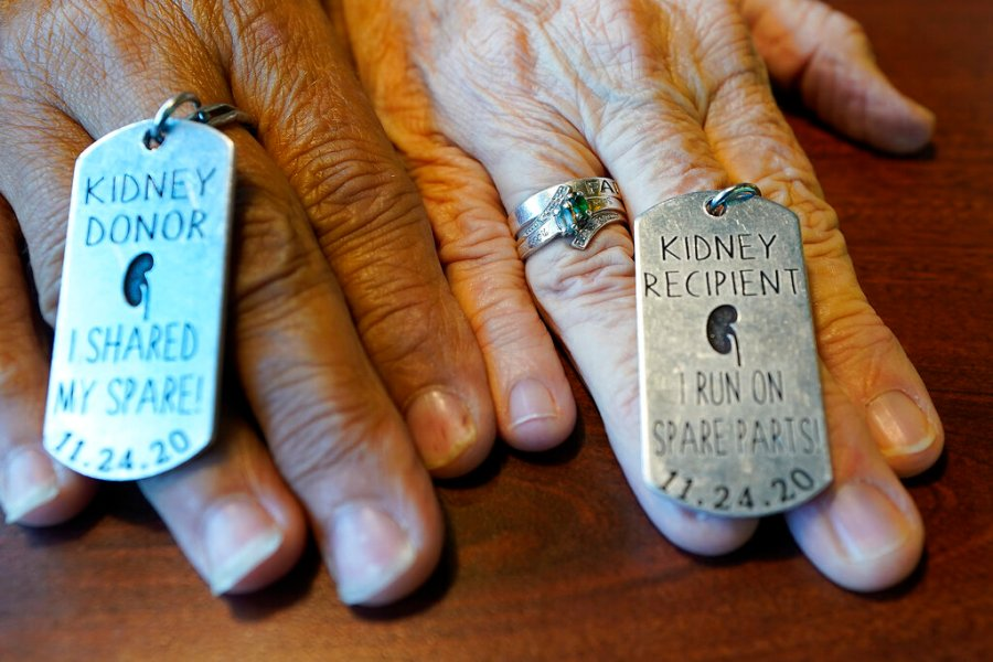 Debby-Neal Stricland and Mylaen Merthe show off donor/recipient tags they had made during a get together Tuesday, May 25, 2021, at a restaurant in Ocala, Fla. Debby, now married to Jim Strickland, donated a kidney to Mylaen Merthe, Jim's ex-wife. (AP Photo/John Raoux)