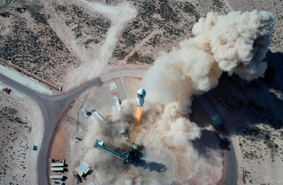 In this photo made available by Blue Origin, the New Shepard NS-14 rocket lifts off from Launch Site One in West Texas on Jan. 14, 2021. On Tuesday, July 20, 2021, Blue Origin's 60-foot New Shepard rocket will accelerate toward space at three times the speed of sound, or Mach 3, before separating from the capsule and returning for an upright landing. (Blue Origin via AP)