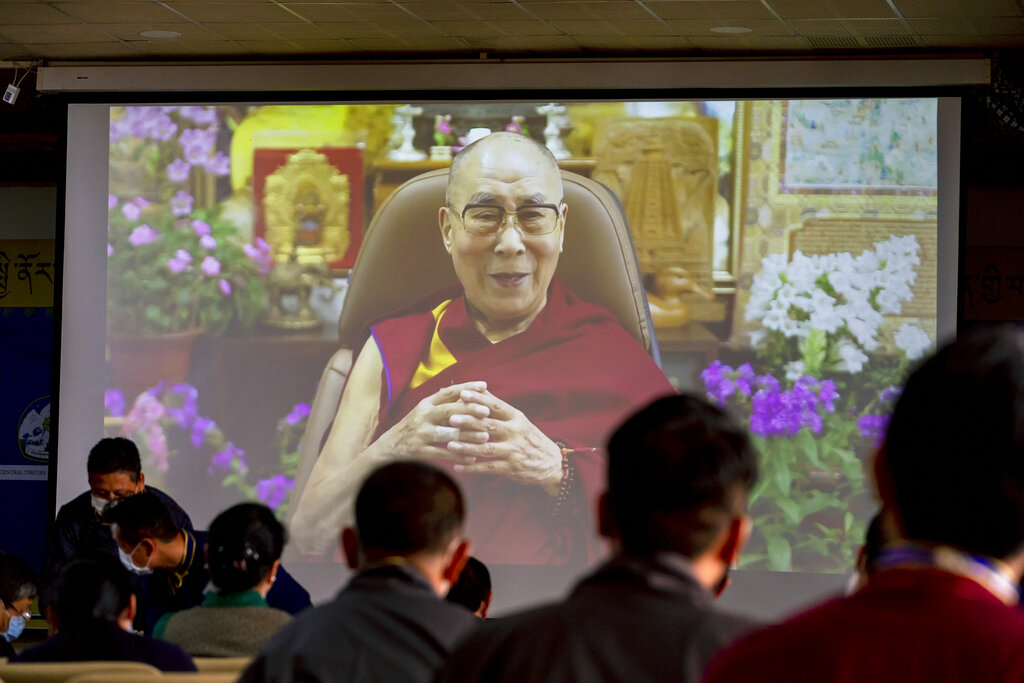 Exiled Tibetan government officials watch a message from their spiritual leader the Dalai Lama on a screen during a ceremony to mark the 86th birthday of the Tibetan leader in Dharmsala, India, Tuesday, July 6, 2021. This year, due to the coronavirus pandemic, the celebrations were muted and behind closed doors. (AP Photo/Ashwini Bhatia)