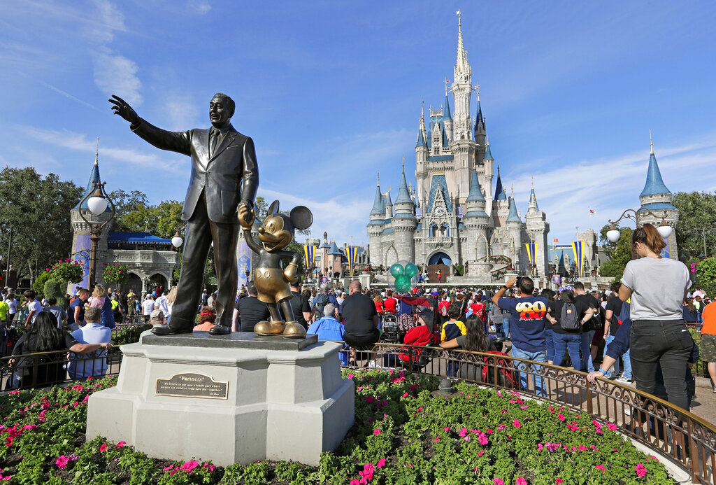 Guests watch a show near a statue of Walt Disney and Micky Mouse in front of the Cinderella Castle at the Magic Kingdom at Walt Disney World in Lake Buena Vista, Fla. (AP Photo/John Raoux, File)
