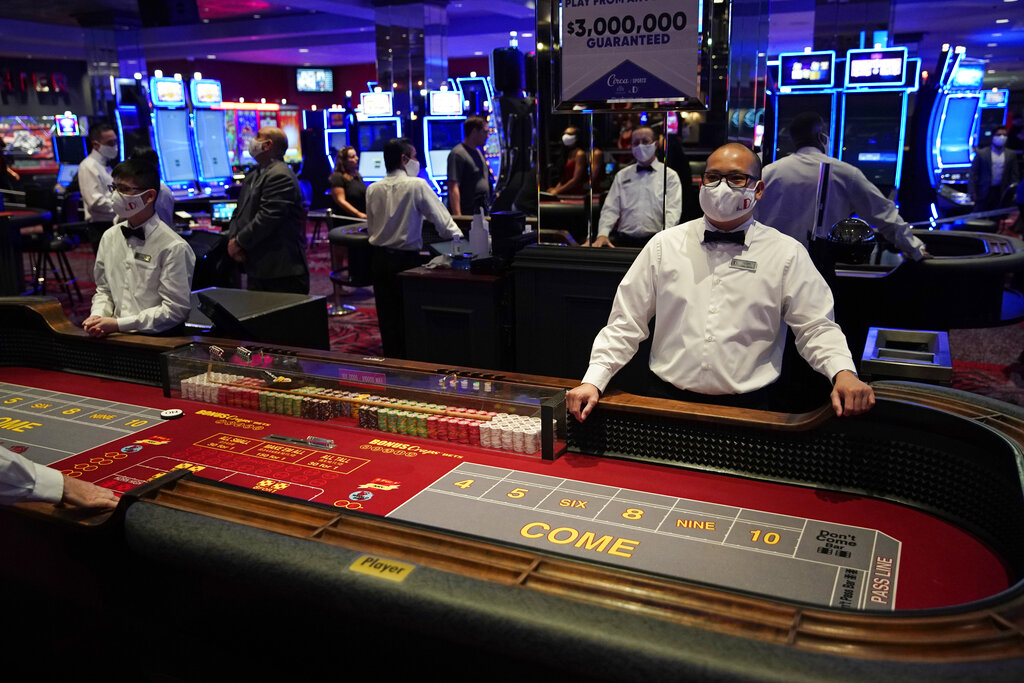 Dealers in masks wait for customers before the reopening of the D Las Vegas hotel and casino in Las Vegas, in 2020. Governments and businesses are scrambling to change course following new federal guidance calling for the return of mask wearing in virus hot spots amid a dramatic spike in COVID-19 cases and hospitalizations nationwide. Nevada and Kansas City were among the locations that moved swiftly to re-impose indoor mask mandates following Tuesday's announcement from the Centers for Disease Control and Prevention. (AP file /John Locher, FIle)