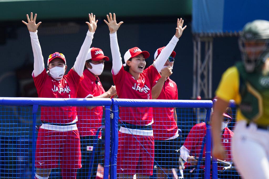 Japanese players celebrate a run by Minori Naito during the softball game between Japan and Australia at the 2020 Summer Olympics, Wednesday, July 21, 2021, in Fukushima, Japan. (AP Photo/Jae C. Hong)