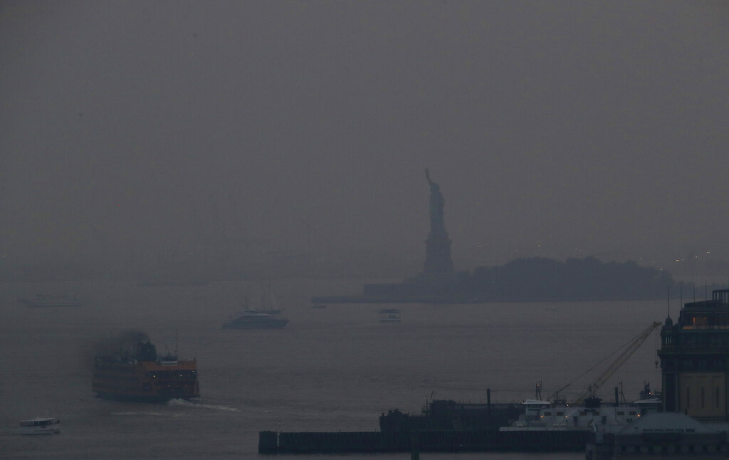 The Staten Island Ferry departs from the Manhattan terminal through a haze of smoke with the Statue of Liberty barely visible, Tuesday in New York. Wildfires in the American West, including one burning in Oregon that's currently the largest in the U.S., are creating hazy skies as far away as New York as the massive infernos spew smoke and ash into the air in columns up to six miles high. (AP Photo/Julie Jacobson)