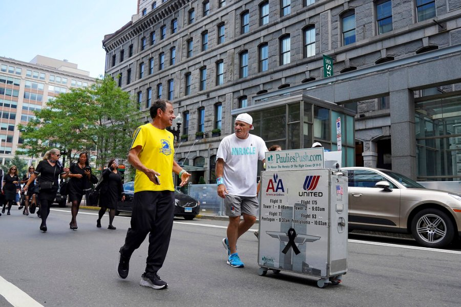 Paul Veneto, right, is joined by Boston Marathon Race Director Dave McGillivray along State Street, in Boston, Saturday, Aug. 21, 2021. Veneto, a former flight attendant who lost several colleagues when United Flight 175 was flown into the World Trade Center on Sept. 11, 2001, is honoring his friends on the 20th anniversary of the terrorist attacks by pushing the beverage cart from Boston to ground zero in New York. (AP Photo/Mary Schwalm)